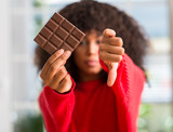 African american woman eating chocolate bar at home with angry face, negative sign showing dislike with thumbs down, rejection concept