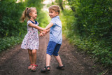 Happy kids walking outdoor at park hold their hands. - 211902896