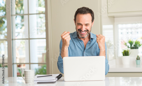 Leinwanddruck Bild Middle age man using laptop at home screaming proud and celebrating victory and success very excited, cheering emotion