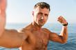 Leinwanddruck Bild - Confident handsome shirtless sportsman taking a selfie