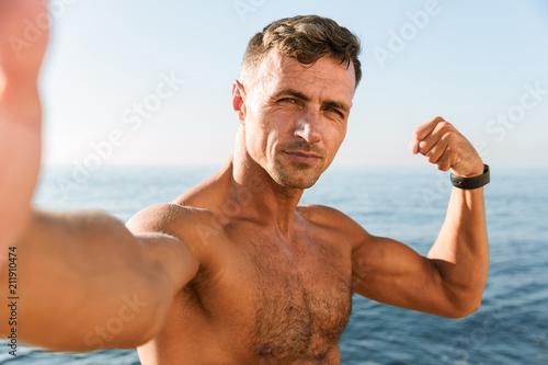 Leinwanddruck Bild Confident handsome shirtless sportsman taking a selfie