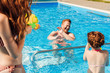 happy young family playing in swimming pool