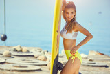 Surfing girl posing in the beach with surfboard - 211912034