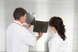 two doctors at the hospital analyze and look at the radiology of a patient - 211921498