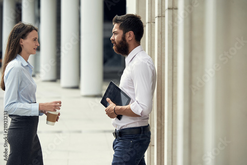 Leinwanddruck Bild Side view of young woman with coffee cup and man with tablet standing on street and talking in relax