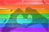 Shadows of hands forming a heart on colorful rainbow painted wood planks background, gay flag and love concept - 211924441
