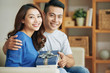 Wonderful happy Asian woman and man embracing on couch and holding decorated gift box smiling at camera