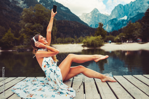 Attractive young woman listen to music on the lake next to the lake - 211931276