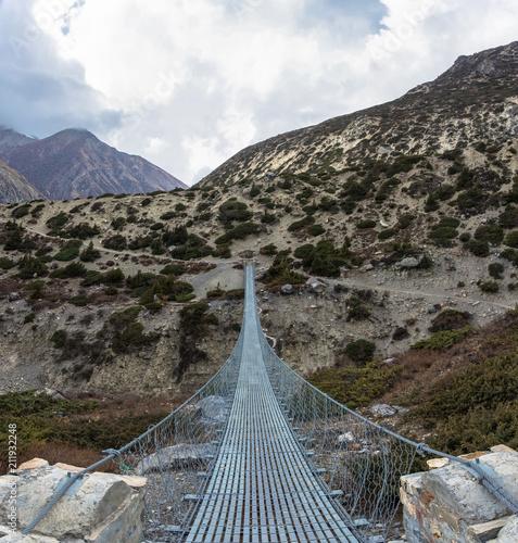 Fototapeta Metal suspension bridge in the Himalayas, Nepal.