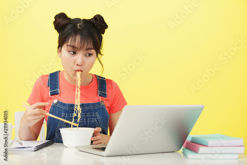 Asian woman sitting at the table with laptop and eating noodles - 211934035