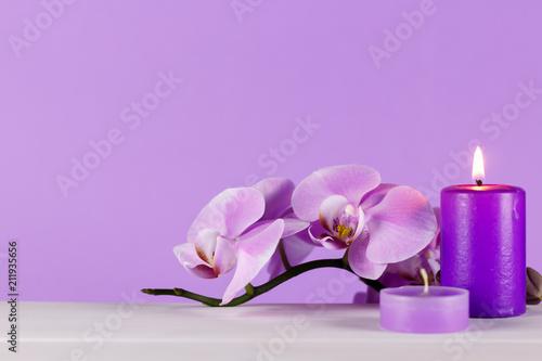 Blada purpurowa orchidea na białym stole z purpurowym tłem. Świece zapachowe na stole zapaliły jedną z dwóch