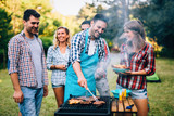 Happy friends enjoying barbecue party - 211940819
