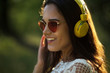 Gorgeous girl in sunnies and headphones. Portrait of beautiful girl with red cat eye shaped sunglasses and big bright yellow headphones. Taken outdoors.