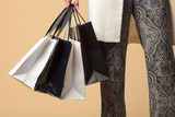 female hand holds many shopping bags isolated on beige background - 211946800