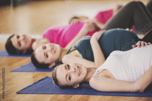 Leinwanddruck Bild Pregnant Women Doing Exercises on Mats in Gym.