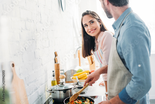 boyfriend frying vegetables on frying pan in kitchen and looking at smiling girlfriend