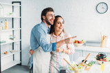 boyfriend pointing on something to girlfriend during cooking in kitchen - 211962853