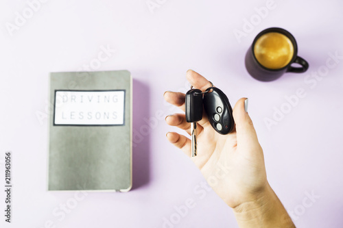 Female hands hold the car keys  Next to the study notebook