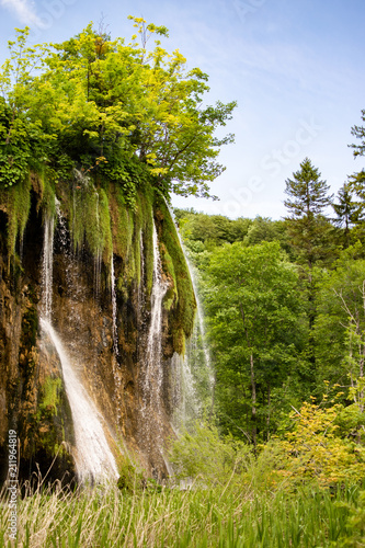 An imposing waterfall with a large flow of water rises through a rock formation in the national park. Photograph taken in the Plitvice natural park in Croatia. - 211964819
