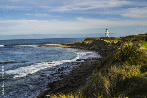 Fotobehang Vuurtoren Travel New Zealand. Scenic view of white lighthouse on coast, ocean, outdoor background. Popular tourist attraction, Waipapa Point Lighthouse located at Southland, South Island. Travel concept.