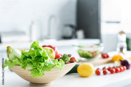 close-up view of bowl with fresh healthy vegetables on kitchen table - 211968246
