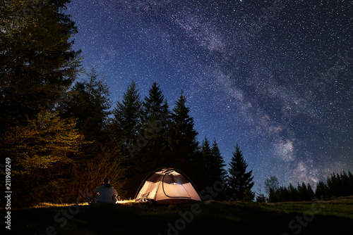 Leinwanddruck Bild Silhouette of male hiker sitting alone near tourist tent at campfire on valley, enjoying night blue starry sky, Milky way, pine trees forest on background. Beauty of nature, mountain camping concept