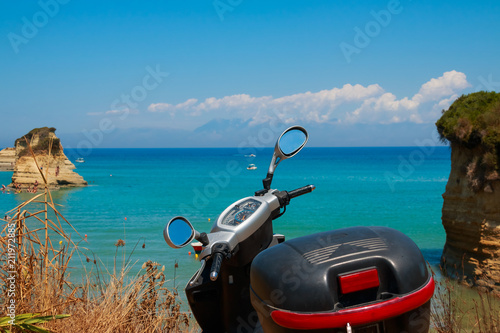 Canvas Scooter motor scooter, motorbike parked on the beautiful coast with amazing view to azure lagoon, gulf.Active summer holiday concept. Rent any transport on your vacation.Scooter on the beach