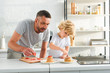 Leinwanddruck Bild - focused little boy with father putting strawberry pieces on pancakes at kitchen