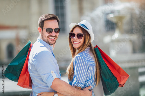 Leinwanddruck Bild Beautiful couple enjoy shopping together, young couple holding shopping bags
