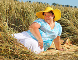 Overweight woman enjoying life during summer vacations. Happy obese farmer relaxing on wheat field. Healthy lifestyle concept. - 211976427