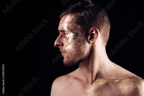 złote spa i zabiegi pielęgnacyjne. złota maska dla skóry człowieka. portret mężczyzny z twarzą. złota ciało sztuki dla człowieka na białym tle na czarnym tle, miejsce. kopanie złota