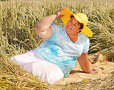 Overweight woman enjoying life during summer vacations. Happy obese farmer relaxing on wheat field. Healthy lifestyle concept. - 211976802