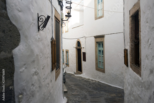Fotobehang Smalle straatjes A view of a narrow street with arch and wooden windows and doors with white wall stone architecture of the island Patmos, Greece
