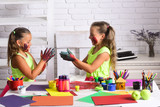 Girls painters painting with gouache paints on table