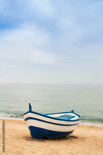 Wooden fishing boat on a sandy beach in sunny day. Place for text - 211989656