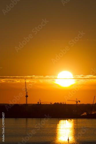 Aluminium Oranje eclat Sunset over the city. Tower crane. Industrial landscape. Bright sunset over the horizon