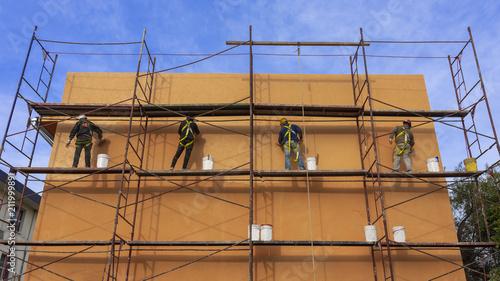 Foto Murales Albañiles colocando revestimiento colorido en frente de edificio