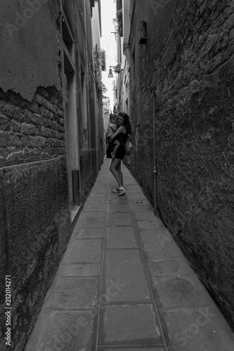 Fototapeta young mother and little daughter posing on a narrow street in venice