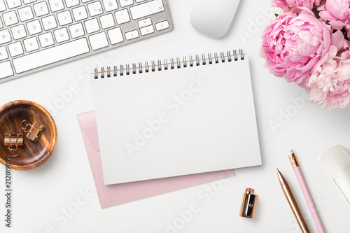 Leinwanddruck Bild feminine workspace / desk with blank open notepad, keyboard, stylish office / writing supplies and pink peonies on a white background, top view