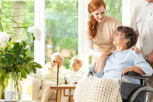 Tender caregiver saying goodbye to an elderly pensioner in a wheelchair in a day care facility.  A companion pushing the wheelchair. Other elderly people in the blurred background. - 212036617