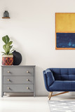 Plant on grey cabinet next to suede sofa under yellow and blue painting in flat interior. Real photo