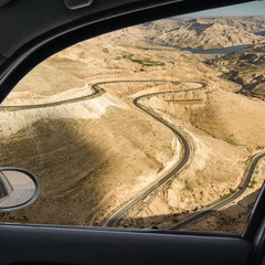 View through the window of a car onto a winding road in the desert landscape of Central Jordan not far from Wadi Mujib Reservoir