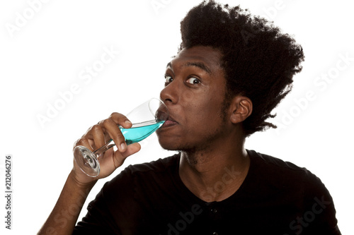 Fototapeta young handsome afro american guy drinks a blue wine isolated on white background. lifestile concept