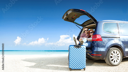 Summer trip on beach. Big blue car with two people. Free space for your text.  - 212046860