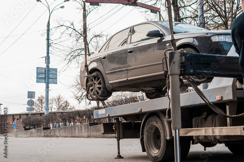 fototapeta na ścianę Evacuation of the car in the city center. The car is lifted to the tow truck