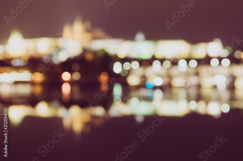 Night view of famous european Prague city - the capital of Czech republic with reflection in river Vltava and historical bridges - blurred defocused background