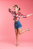 Happy young pin-up woman posing isolated
