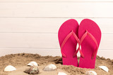 flip flops with sand and shellfish with white wooden background and copyspace - 212064621