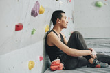 Side view of pensive Asian man sitting on mat in clambering gym leaning on wall and looking away in leisure - 212067217