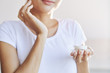 Crop female in white t-shirt taking care of skin putting cream on face on light blur background